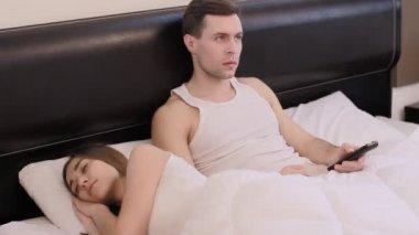 Guy is watching TV while his girlfriend is sleeping — Stock Video