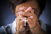 Praying with a rosary — Stok fotoğraf
