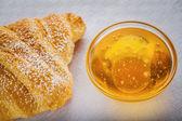 Tarro de miel y un croissant — Foto de Stock