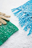 Gloves and scarves of wool over the snow — Stock Photo