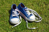 Old childrens sneakers on grass background — Stock Photo