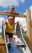 Two boys playing on a playground slide — Stock Photo