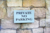 Private no parking sign on stone wall — Foto Stock