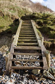Wooden steps leading down to a pebbled beach — Stock Photo