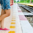 Girl waiting for the Train behind yellow line — Stock Photo