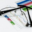 Broken black glasses on business graph — Zdjęcie stockowe #37289779