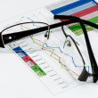 Foto Stock: Broken black glasses on business graph