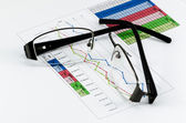 Broken black glasses on business graph — Stok fotoğraf