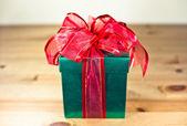 Green box red bow and ribbon — Stock Photo