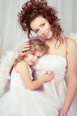 The girl embraces the child of an angel — Stock Photo