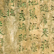 Ancient worn wall full of green chinese text — Foto Stock