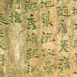 Ancient worn wall full of green chinese text — Stock Photo