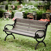 Empty old wooden bench in cemetery — Stock Photo