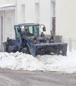Snowplow cleaning a city street in snowfall — Stock Photo