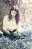 Girl reading a book under a tree in nature — Stock Photo