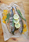 Fresh fish on wooden kitchen board with, rosemary, lemon and colorful peppercorns on wooden background. Culinary healthy cooking. — Stock Photo