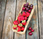 Strawberry and sweet cherry in a wattled basket on a wooden table — Stock Photo