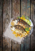 Two fried fish with fresh herbs and lemon on wooden table — Stock Photo