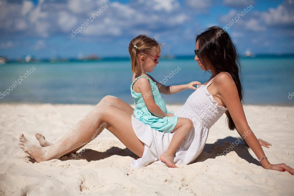 年轻漂亮的妈妈和她可爱的小女儿在热带海滩