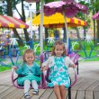 Two little fashion lovely sisters ride on the carousel in the park — Stock Photo #26636045