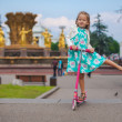 Стоковое фото: Cheerful cute toddler girl on scooter in park