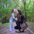 Cute little girl kissing her mother's nose — ストック写真