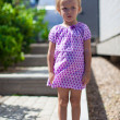 Stock Photo: Serious little girl stands in front of her home