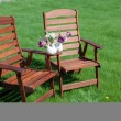 Two wood chairs on the grass with vase of flowers on them — Foto Stock