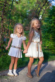 Two fashion cute sisters go hand in hand in the park — Stock Photo