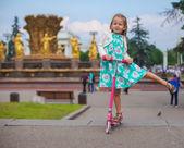 Chica alegre niño lindo de la moto en un parque — Foto de Stock