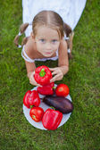 Little girl with pigtails in a garden with a plate of vegetables — Stock Photo