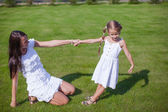 Young happy mother and her daughter having fun in the yard — Stock Photo