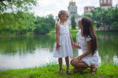 Young mother and her daughter having fun near the lake — Stock Photo