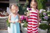 Ellerinde çiçeklerle country bahçesinde tatlı küçük kızlar — Stok fotoğraf