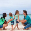 Young beautiful family with two daughters having fun at beach — Stock Photo #26786717