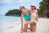 Young mother and her little daughter in hats have fun on beach — Stock Photo