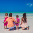 Rear view of young family with two kids on caribbean beach vacation — Stock Photo #27017441