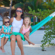Fashion mother and  her daughters relaxing in hammock in exotic resort — Stock Photo