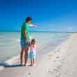 Rear view of young father with his daughter shows in the sea — Stock Photo #27019005