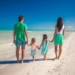 Back view of family of four walking along the beach — Stock Photo #27019309