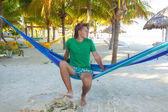 Young man sitting in hammock on the beach and looking at the sea — Stock Photo