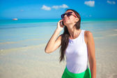 Young beautiful woman talking on her phone on the beach — Stock Photo