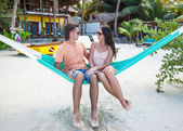 Young couple sitting in hammock on the beach and looking each other — Stock Photo