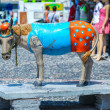 Stockfoto: Multicolored figure of donkey into port on Santorini island
