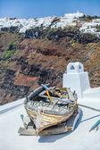 Famosa vecchia barca sul tetto di casa sullo sfondo di imerovigli — Foto Stock