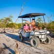 Dad with his two daughters driving golf cart at tropical beach — Stock Photo