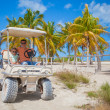 Dad with his two daughters driving golf cart at tropical country — Stock Photo