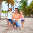 Young dad and his cute fashion daughters on tropical sand bech in palm grove — Stock Photo #27679397