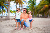 Young dad and his cute fashion daughters on tropical sand bech in palm grove — Stock Photo