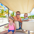 Young father and his little daughters inside golf cart at tropical country — Stock Photo